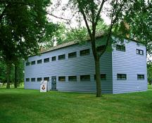 Rear view of the Men's Two-Storey Barracks, showing regular, horizontally aligned windows and a low, hipped roof, 1994.; Parks Canada Agency / Agence Parcs Canada, B. Morin, 1994.