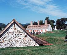 General view of the Fort Anne National Historic Site of Canada showing some surviving remnants of the original fort such as the Powder Magazine (left) and the Officer's Quarters (right), 1977.; Parks Canada Agency / Agence Parcs Canada, T. Grant, 1977.