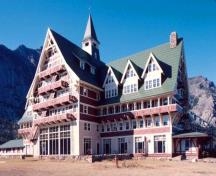 General view of the Prince of Wales Hotel National Historic Site of Canada showing its Swiss chalet motifs, pitched gabled roofs, two-storey dormers, tiers of continuous balconies, and the use of contrasting finish colours, 1995.; Parks Canada Agency/Agence Parcs Canada, 1995.
