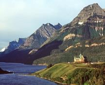 Panoramic view of the Prince of Wales Hotel emphasizing its spectacular siting on a promontory overlooking Waterton Lake and its viewscapes of the surrounding prairies, mountains and lakes, 1999.; Parks Canada Agency / Agence Parcs Canada, J.F. Bergeron. 1999.