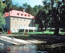 Corner view of the river side of the Carillon Barracks showing the location of the building on the banks of the Ottawa River, next to the Carillon Canal, 1989.; Parks Canada Agency/ Agence Parcs Canada, 1989.