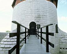 Detail view of Shoal Tower entrance showing the defensive design evident in the high entrance, smooth walls, bomb-proof construction with thick stone walls at the base, the tin-clad roof and the fireproof nature of its materials, 1982.; Parks Canada Agency / Agence Parcs Canada, F. Cattroll, 1982