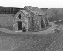 General view of the Powder Magazine, showing the sturdy thick-walled masonry construction, which is typical of the work of the Corps of Royal Engineers, 1989.; Parks Canada Agency / Agence Parcs Canada, 1989.