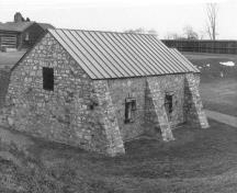 Rear view of the Powder Magazine, showing the exterior massing with reinforcing buttresses, 1989.; Parks Canada Agency / Agence Parcs Canada, 1989.