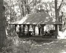 View of the Aubrey Island Picnic Shelter, showing the hipped roof, vertical wood supports and wood brackets, 1992.; Archaeological Services and Historica Resources, Ltd., 1992.