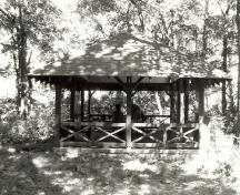 Side view of the Aubrey Island Picnic Shelter, showing the low surrounding railing of crossed timbers, 1992.; Archaeological Services and Historica Services, Ltd., 1992.