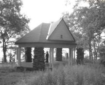 General view of the Gordon Island Pavilion, showing the decorative exposed rafter ends and the low wooden railing, 1992.; Archeological Services and Historica Resources Ltd., 1992.