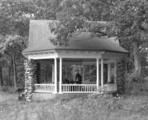 Side view of the Gordon Island Pavilion, showing the medium-pitched, octagonal roof structure supported by an articulated box beam, which in turn, is supported at the perimeter by slender paired wooden Doric columns, 1992.; Archeological Services and Historic Resources Ltd., 1992.