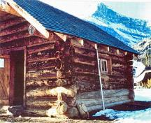 Corner view of the Halfway Hut showing the use of natural, local materials consistent with the principles of rustic architecture such as the horizontally laid peeled log construction, boulder foundation, and wood shingle roof.; Western Canada Service Center / Centre de services de l'Ouest canadien, n.d.