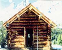 Front facade of the Halfway Hut showing the deep overhang above the cabin entrance.; Parks Canada Agency / Agence Parcs Canada, n.d.