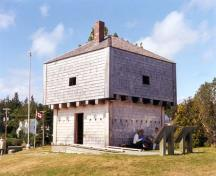 Corner view of St. Andrews Blockhouse, showing the squat square profile, pyramidal roof, entrance and the artillery gunports, machicolation loopholes and musketry holes, 1998.; Parks Canada Agency/Agence Parcs Canada, 1998.