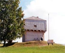 General view of the rear and side elevations of the St. Andrews Blockhouse showing the simple, well-proportioned, geometric massing of the squat square profile with a pyramidal roof, 1998.; Parks Canada Agency/ Agence Parcs Canada, 1998.