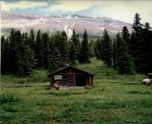View of the main entrance to the Byng Warden Patrol Cabin, showing the log-framed open porch with trussed-purlin supports and posts at the gable end, 1997.; Parks Canada Agency / Agence Parcs Canada, 1997.