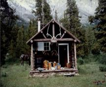 Front elevation of the Topaz Warden Patrol Cabin, showing the gable roof and log-framed open porch with trussed-purlin supports and posts at the gable end, 1997.; Parks Canada Agency / Agence Parcs Canada, 1997.