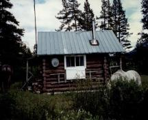 Side view of the Topaz Warden Patrol Cabin, showing the walls of peeled 8-10 inch logs, horizontally laid and saddle- notched at the corners, 1997.; Parks Canada Agency / Agence Parcs Canada, 1997.