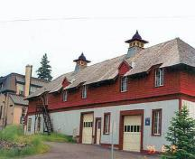 Corner view of the north elevation of the Service Building showing the shingled hip roof with a broad overhang and carved brackets, decorated roof ventilators, dormers and cut-away eaves over the windows, 1995.; Parks Canada Agency / Agence Parcs Canada, C. Zacconi, 1995.