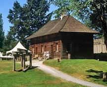 Corner view of the Servants' Quarters showing its one-and-a-half storey, hipped roof, rectangular structure that is five bays in length and two bays in width, 2002.; Parks Canada Agency / Agence Parcs Canada, M. Trepanier, 2002.