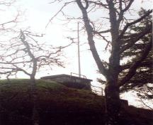 General view of the Battery Commander's Post showing the simple, single-storey, flat roofed massing of the structure that is partially concealed by an earth embankment, 1997; Parks Canada Agency / Agence Parcs Canada, J. Mattie, 1997.