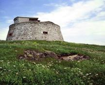 General view of the Carleton Martello Tower showing the simple geometric massing of the squat cylindrical tower, 1983.; Agence Parcs Canada / Parks Canada Agency, F. Catroll, 1983.