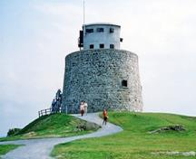 General view of the Carleton Martello Tower showing the exterior walls built of rubble masonry which inclines slightly inwards as it rises to a parapet wall which is in turn topped by a two-storey concrete observation post, 1983.; Parks Canada Agency / Agence Parcs Canada, J. Steeves, 1983.