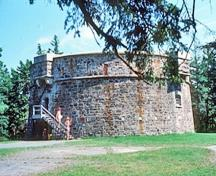 General view of the Prince of Wales Martello Tower showing the simple geometric massing of the squat cylindrical tower of solid stone construction with a low profile, 1977.; Parks Canada Agency / Agence Parcs Canada, T. Grant, 1977.