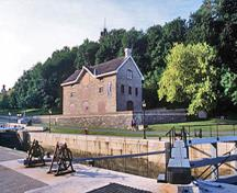 General view of the Commissariat Building emphasizing its imposing position within the Colonel By Valley, facing the Rideau Canal and overlooking its northern entrance, 2002.; Parks Canada Agency / Agence Parcs Canada, A. Guindon, 2002.