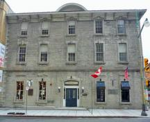General view of the main facade of the Former Geological Survey of Canada Building showing its modest classically inspired ornamentation including semi-arched window lintels, keystones, broad stone stringcourses, stone quoins, 2011.; Parks Canada Agency / Agence Parcs Canada, M. Therrien, 2011.