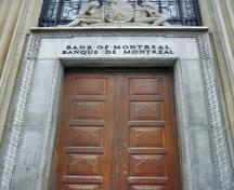 General view of the Bank of Montreal, showing its central doorways with a carved moulding and a superimposed sculpture of the bank's coat of arms above, 2011.; Parks Canada Agency / Agence Parcs Canada, M. Therrien, 2011.