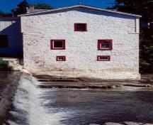 Side view of the Légaré Mill, showing its heavy walls with small window openings, 1999.; Parks Canada Agency / Agence Parcs Canada, 1999.