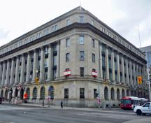 General view of the Wellington Building showing the strong base storey with round-headed openings, a grand three-storey centre portion marked by Corinthian colonnades and pilasters, and a substantial cornice and parapet, 2011.; Parks Canada Agency / Agence Parcs Canada, M. Therrien, 2011.