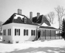 Side view of the Big House, showing the colombage pierroté of the annex, which consists of a heavy oak timber frame infilled with rubblestone and mortar and finished in stucco, 1989.; Parks Canada Agency / Agence Parcs Canada, K. MacFarlane, 1989.