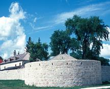 General view of the rear of the Southwest Bastion showing the stone walls, wood shingle roof and dormer siding, 1997.; Parks Canada Agency / Agence Parcs Canada, S. Buggey, 1997