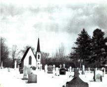 This historic image from circa 1940 shows the cemetery with the church in the background; Queens County Heritage Collection