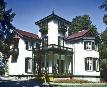 General view of Bellevue House showing the original Italianate proportions of its silhouette with a high square tower, balconies and a columned verandah, 1985.; Parks Canada Agency / Agence Parcs Canada, B Morin, 1985.