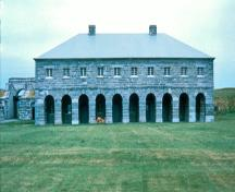 General view of Fort Lennox showing the buildings, their stone construction, their volume, mass, roof type, window and door placements.; Parks Canada Agency / Agence Parcs Canada.