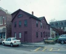 View of the exterior of Sinclair Inn / Farmer's Hotel, showing its rectangular, two-and-a-half-storey massing under a front-sloping gable roof.; Parks Canada Agency / Agence Parcs Canada.