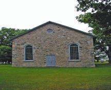 General view of Old Stone Church, showing its end-gable entrance with a central door flanked by two large multi-pane windows, 2006.; Parks Canada Agency / Agence Parcs Canada.