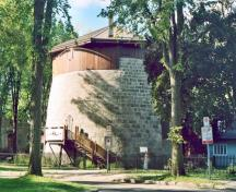 General view of Québec Martellow Towers, showing their squat, cylindrical, two-storey massing with slightly inclining exterior walls, 2003.; Parks Canada Agency / Agence Parcs Canada, 2003.