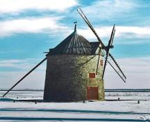 Side view of Round Stone Windmill and House, showing the tall cylindrical three-and-a-half storey massing of the mill under a high conical cap pierced by triangular dormers, 1995.; Parks Canada Agency / Agence Parcs Canada, 1995.