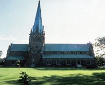 Side view of Christ Church Cathedral, showing its picturesque siting on a green sward.; Parks Canada Agency / Agence Parcs Canada.