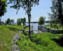 General view of Carillon Canal, showing the relationship between the superintendent's residence, the old house of the toll collector, the entry to the first canal and lock number one of the second canal, 2003.; Parks Canada Agency / Agence Parcs Canada.