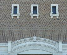 Detail view of Royal Theatre, showing ground floor terra cotta facing laid to resemble stone, the polychrome and banded, diamon-patterned brickwork, 2011.; Parks Canada Agency / Agence Parcs Canada, Andrew Waldron, 2011.