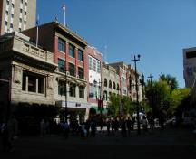General view of Stephen Avenue, showing the regular pattern of large windows - either flat or round-headed - defining the street facade of each building, 2004.; Parks Canada Agency/Agence Parcs Canada, 2004.