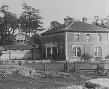 General view of the Admiral's Residence and Former Naval Storekeeper's House, showing the rectangular, two-storey form of the building executed in brick and stone.; British Columbia Archives and Records Service, / Archives et Service des documents de la Colombie-Britannique, HP 7856.