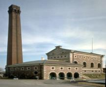 View of the Hamilton Waterworks complex, showing the tall chimney and the distinctive Italianate profile of the original waterworks pumphouse, 1993.; Parks Canada Agency/Agence Parcs Canada, 1993.
