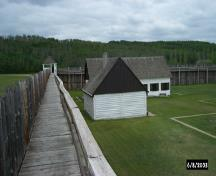 View of building and stockade catwalk inside the fort; Parks Canada / Parcs Canada, 2003