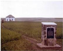 The Fort Pitt plaque erected by the Province of Saskatchewan in 1973 showing the reconstructed factor's house in background; Parks Canada / Parcs Canada,