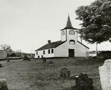 View of the Little Dutch (Deutsch) Church, showing its collection of early grave markers, haphazardly set within the uneven, sloping ground, 1965.; Parks Canada Agency / Agence Parcs Canada, 1965.