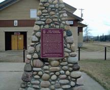 The cairn and HSMBC plaque for Fort Assiniboine NHS. The legion building is behind the cairn.; Parks Canada / Parcs Canada, 1989