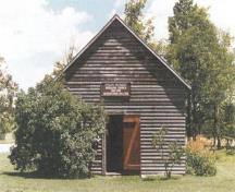 View of the main entrance of the Oro African Methodist Episcopal Church, showing its squared-log, solid wall construction, wood shingle roof, and the wood detailing of the doors, 1999.; Parks Canada Agency / Agence Parcs Canada, Owen Thomas, 1999.